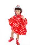 中国小女孩佩带的雨衣和起动 库存图片
