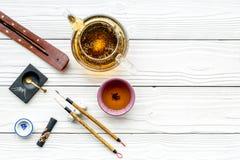 中国或日本传统 书法和茶道概念 特别书写笔、墨水在茶壶附近和杯子  免版税库存图片