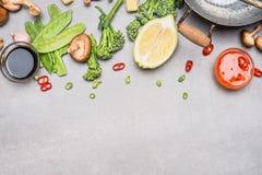 中国或泰国烹调在灰色石背景,顶视图的烹调菜和香料成份 库存图片