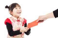 中国新年好 小女孩接受了红色信封 免版税库存图片