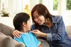 中国母亲和儿子坐沙发 免版税库存照片