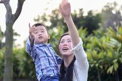 中国母亲和孩子提高了他们的手和展示某事 他们在公园走 免版税库存图片