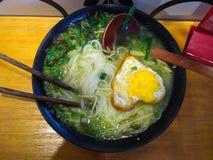 中国汤面用心形的鸡蛋和绿色菜在一个黑碗 库存照片