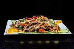 中国烹调、煮沸的牛肉用黄瓜和蕃茄在白色板材,在黑背景 免版税库存图片