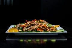 中国烹调、煮沸的牛肉用黄瓜和蕃茄在白色板材,在黑背景 免版税库存照片