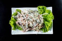 中国烹调,沙拉用蘑菇,油煎了牛肉,腌汁,在一块白色板材的莴苣在黑背景 库存照片