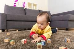 中国男婴戏剧玩具块和说谎在地毯 免版税图库摄影