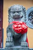 中国皇家狮子雕象,与红色弓的中国监护人狮子在胸口 库存图片