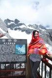 中国秀丽佩带红色方巾游览玉龙雪山 库存图片