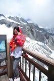 中国秀丽佩带红色方巾游览玉龙雪山 库存照片