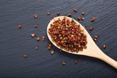 中国胡椒,在木匙子的四川胡椒在黑板岩石头板材 免版税库存图片