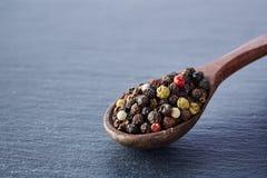中国胡椒,在木匙子的四川胡椒在黑板岩石头板材 免版税库存照片