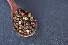 中国胡椒,在木匙子的四川胡椒在黑板岩石头板材 库存图片
