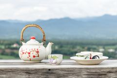 中国茶壶和茶杯在木桌和山风景 免版税库存图片