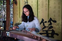 中国,上海- 2017年11月7日:中国女孩演奏Guzheng或郑 被采的汉语弹吉舍尔琴传统 免版税图库摄影