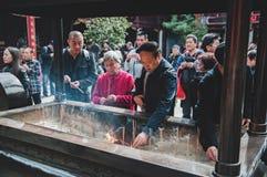 中国,上海- 2017年11月7日:亚裔人民祈祷在一根佛教寺庙和灼烧的香火棍子 库存图片