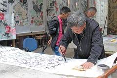 中国,苏州- 2012年4月14日 一个人在奇恩角写书法 库存图片