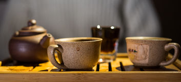 中国黏土托起木饮用的糖表茶的茶壶二 夜间 普洱哈尼族彝族自治县 茶书桌 杯子 免版税图库摄影