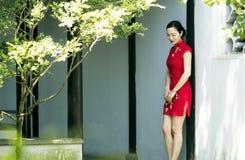 中国cheongsam模型在中国古典庭院里 库存照片