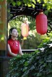 中国cheongsam模型在中国古典庭院里 免版税库存照片