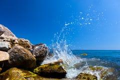 击中在一个热带海滩的波浪岩石 希腊santorini 免版税图库摄影