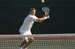击中在法院的网球员反手 免版税库存照片