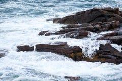 击中在海滩的海波浪岩石 库存图片