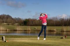 击中在航路的女子高尔夫球运动员高尔夫球 免版税库存图片