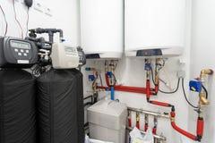 中央水力锅炉照片在有红色管子发热设备和聪明的控制板的轻的明亮的室 免版税库存图片