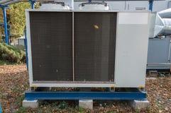 中央通风系统的灰色商业冷却装置与站立大透气的单位室外在fa包括的地面上 免版税库存图片