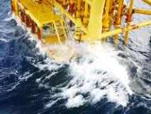 击中小船着陆和生产槽孔的高波浪在近海平台 库存照片