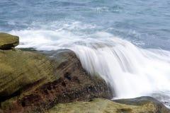 击中岸岩石的海波浪 免版税库存图片