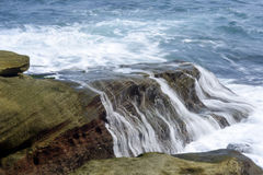 击中岸岩石的海波浪 免版税库存照片