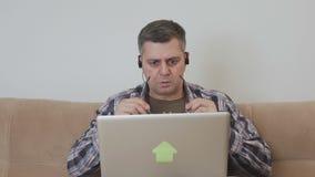 中年人坐有膝上型计算机情感地做鬼脸的神色的长沙发在屏幕 影视素材