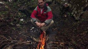 中年人由火坐在森林里 股票视频