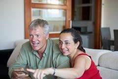 中年夫妇看一看在家电视和愉快赢得 免版税图库摄影