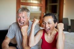 中年夫妇看一看在家电视和愉快赢得 免版税库存图片