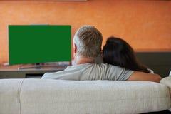 中年夫妇看一看在家电视 库存照片