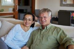 中年夫妇看一看在家电视 免版税库存图片