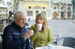 中年妇女和她的年长丈夫户外一起坐在与大阳台的咖啡馆的消费时间户外和 免版税库存图片