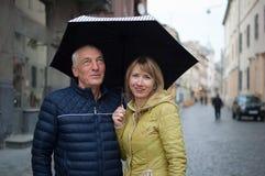 中年妇女和她的年长丈夫户外一起站立在他们的在被铺的街道上的伞下的消费时间 库存图片