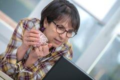 中年妇女喝一杯咖啡 免版税库存照片