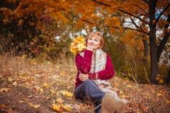 中年妇女在秋天森林里放松 免版税库存图片