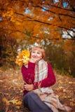 中年妇女在秋天森林里放松 图库摄影