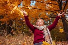 中年妇女投掷的叶子在森林里 免版税库存照片