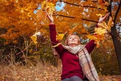 中年妇女投掷的叶子在森林里 库存照片
