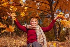 中年妇女投掷的叶子在森林里 库存图片