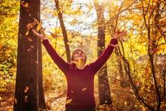 中年妇女投掷的叶子在森林里 图库摄影