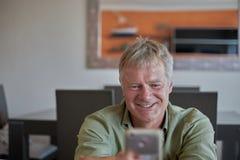 中年帅哥在家有智能手机机动性的 免版税图库摄影
