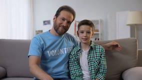 中年志愿拥抱的青春期前的男孩和看对照相机,孤儿关心 股票录像